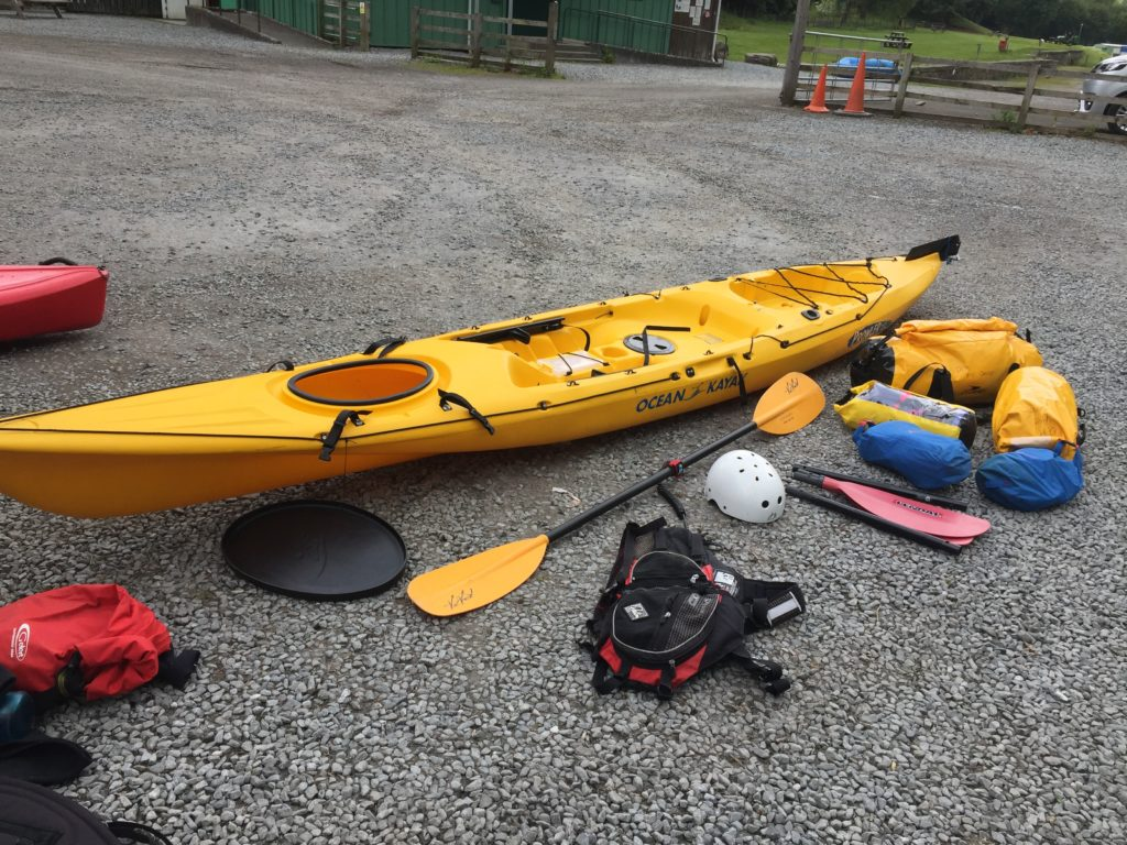 Packing gear into waterproof bags to fit in hatch of kayak