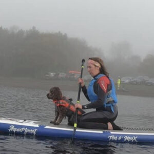 owner and dog paddleboarding together