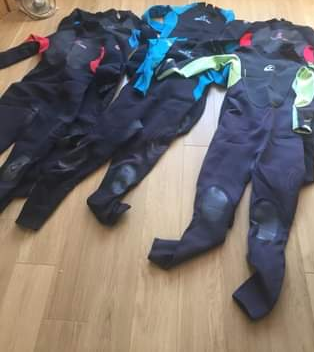 pile of wetsuits